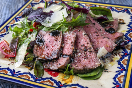 Traditional Italian Tagliata di Manzo Steak with Parmesan and Salad as close-up on a plate Reklamní fotografie