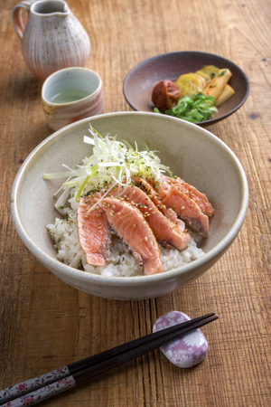 thinly: Traditional Japanese Hokkaidon Thinly Sliced Salmon Donburi as close-up in a bowl