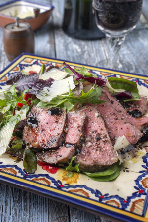 Traditional Italian Tagliata di Manzo Steak with Parmesan and Salad as close-up on a plate Standard-Bild
