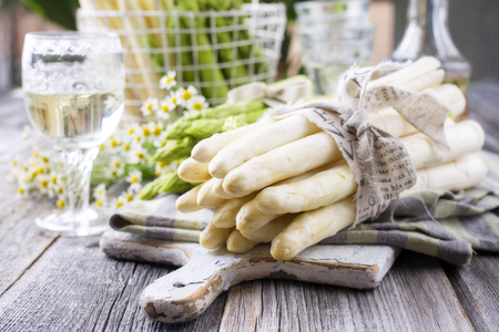 Row of green and white asparagus as close-up on a cutting board