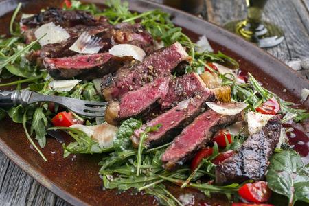 전통적인 이탈리아 Tagliata 스테이크 접시에 클로즈업으로 파 르 마와 샐러드