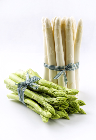 Fresh green and white asparagus bundle as close up with ribbon - covered on white background Standard-Bild