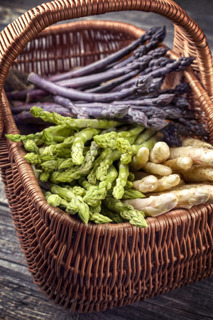 Fresh raw white, green and purple asparagus as close-up in a basket