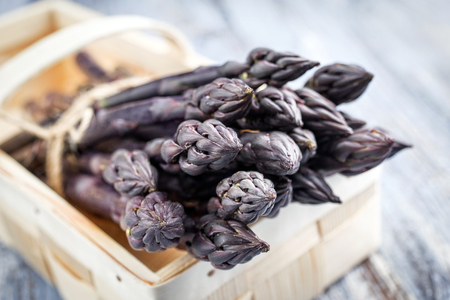 delikatesse: Row purple Asparagus as close-up in a basket
