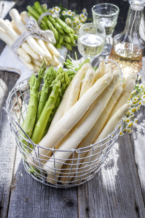 white wine: Row green and white Asparagus as close-up in a basket