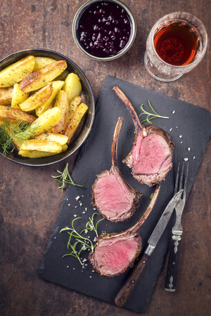 Barbecue Rack of Venison with Roast Potatoes and Cranberries on a black slate