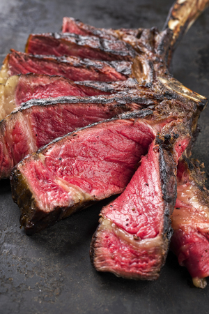 Barbecue dry aged Wagyu Tomahawk steak sliced ??as close-up on old metal sheet