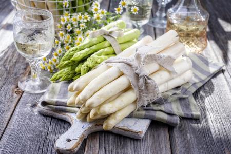 Rij van groene en witte asperges als close-up op een snijplank Stockfoto