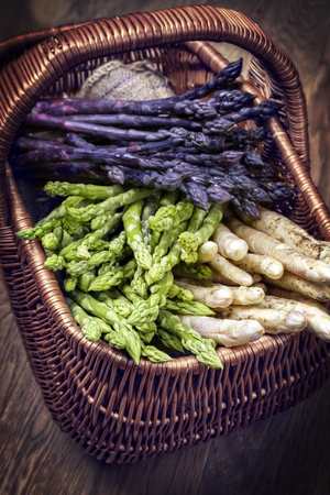 basketry: Fresh raw white, green and purple asparagus as close-up in a basket