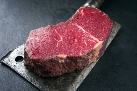 Dry aged raw Kobe Point steak as close-up on a kitchen cleaver Stock Photo