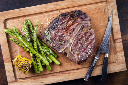 Barbecue dry aged Wagyu Porterhouse Steak with green Asparagus as close-up on a cutting board Stok Fotoğraf