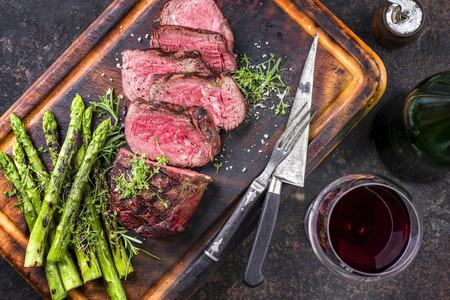 グリーン アスパラガスの焼きまな板の上のクローズ アップとしてバーベキュー和牛ポイント ステーキ