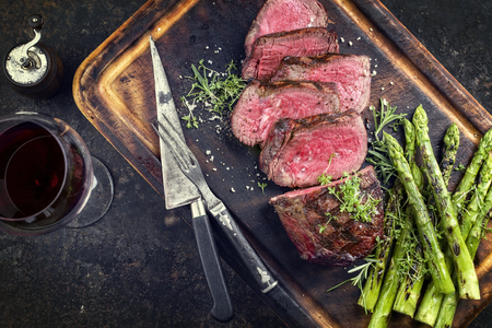 Barbecue Wagyu Point Steak with green asparagus as close-up on burnt cutting board Stok Fotoğraf - 81545393