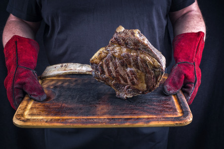 Man is holding barbecue Wagyu Tomahawk Steak on old burnt cutting board in his hands with gloves
