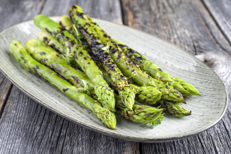 Barbecue groene asperges als close-up op een bord
