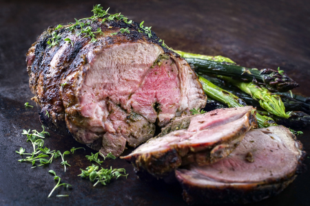 Barbecue Lamb Roast with green asparagus as close-up on an old metal sheet Stok Fotoğraf