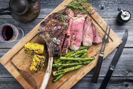 Barbecue Wagyu Tomahawk Steak with green Asparagus and Corn as a top view on a cutting board