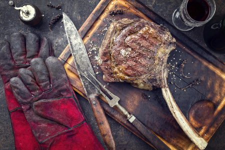 Barbecue Wagyu Tomahawk Steak as a top view on burnt cutting board