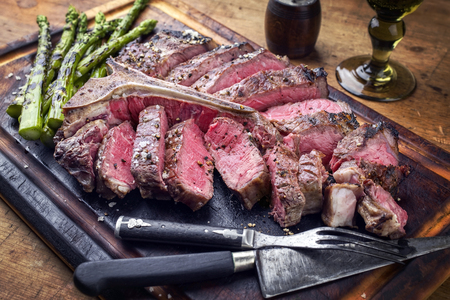 Barbecue dry aged Wagyu Porterhouse Steak sliced ??with green Asparagus on a cutting board