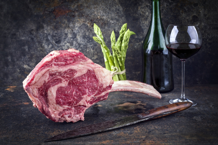 Raw dry aged Wagyu Tomahawk steak with green asparagus and redwine as close-up on old metal sheet Stock Photo