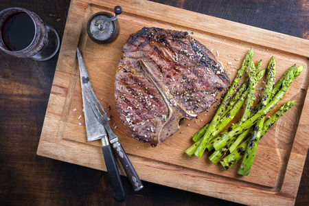 Barbecue dry aged Wagyu Porterhouse Steak with green Asparagus as close-up on a cutting board Banco de Imagens