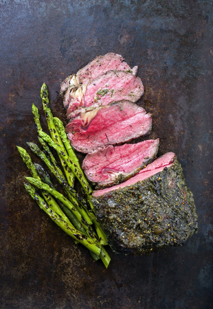 Barbecue Wagyu Roast Beef with green asparagus as close-up on old metal sheet Stock Photo