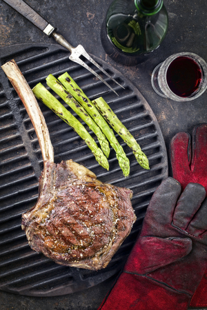 Barbecue Wagyu Tomahawk Steak with green Asparagus as top view on used grillage