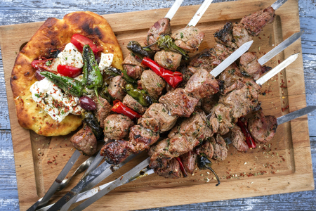 Traditional Greek Souvlaki with Feta and Pita Bread as a top view on an old burnt cutting board