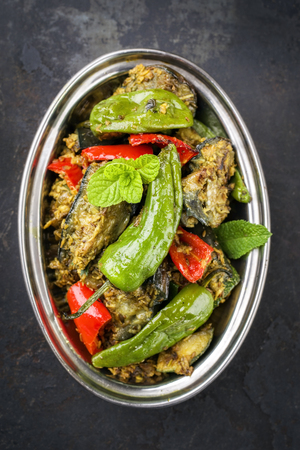 Indian Vegetable Curry Fry with Eggplant and Sweet Peppers as close-up in a Korai Standard-Bild
