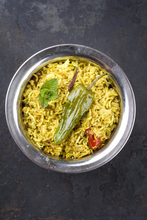 Indian Vegetable Biryani with sweet peppers as close-up in a Korai