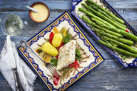 Codfish fillet with green asparagus and boiled potatoes as top-view on a plate Stock Photo