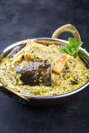 Traditional Indian Vegetable Curry with Sweet Potatoes and Eggplant as close-up in a Korai
