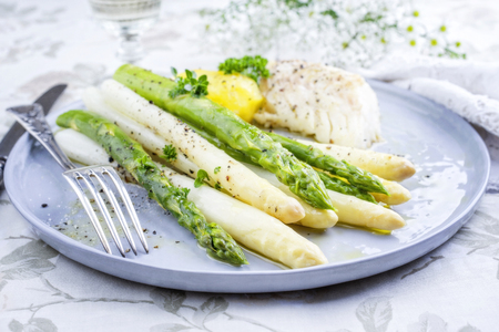 Codfish fillet with green and white asparagus and boiled potatoes as top-view on a plate Stock Photo