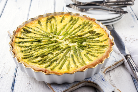 leger: Tart with green asparagus on backing form as top view on wooden table