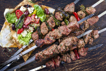 Traditional Shashlik with Salad and Yufka Bread as a top view on an old burnt cutting board Imagens