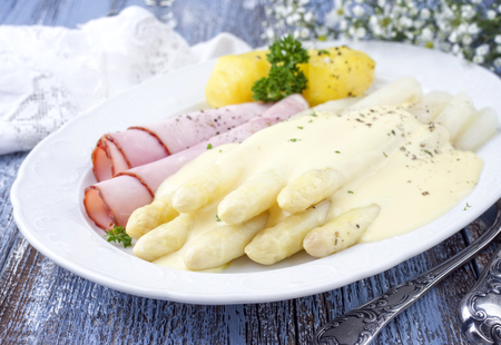 White asparagus with ham and boiled potatoes as top-view on a plate