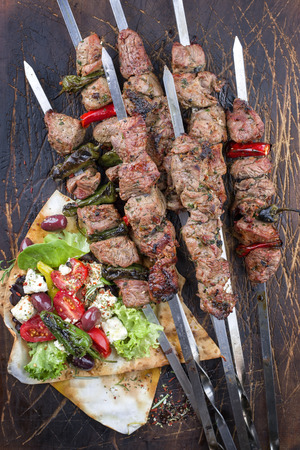 Traditional Shashlik with Salad and Yufka Bread as a top view on an old burnt cutting board Zdjęcie Seryjne