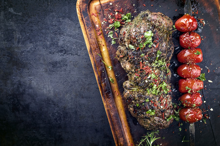Barbecue Lamb Roast with skewered tomatoes as close-up on an old burnt cutting board