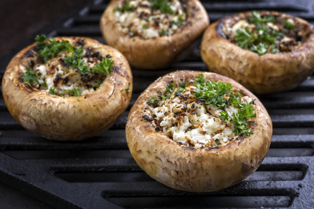 Traditional Italian Mushroom Caps stuffed with Feta as close-up on a grillage