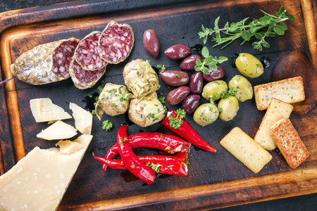 Traditional Italian Antipasti with Salami and Vegetables as a top view on old burnt cutting board