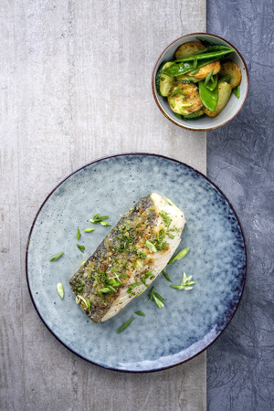 Japanese Fried cod fish fillet with vegetable and potatoes as top-view on a plate