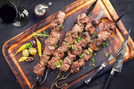 Traditional Russian shashlik on a barbecue skewer and red wine as a top view on an old burnt cutting board