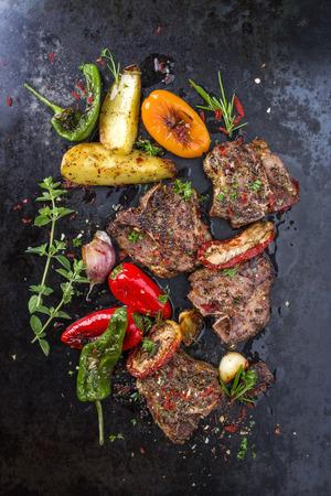 Barbecue T-bone lamb steak with Vegetable and seasonings on a rusty metal sheet