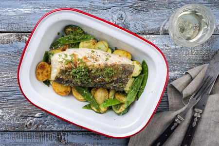 Fried cod fish fillet with potato and potatoes as a top view in a roasting tin Stock Photo