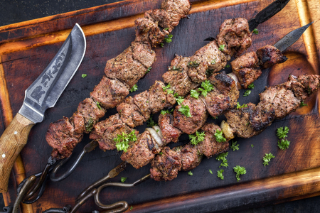 Traditional Russian shashlik on a barbecue skewer as a top view on an old burnt cutting board