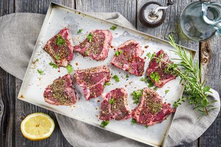 Raw T-Bone Lamb Steak with Seasonings Foto de archivo