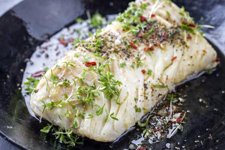 Gebraden kabeljauw visfilet met kruiden en kers als close-up in een gietijzeren pan