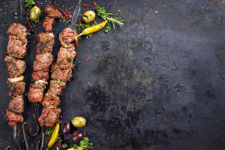 Traditional Russian shashlik on a barbecue skewer as a top view with copyspace on old rusty metal sheet