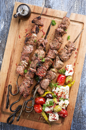 Traditional Greek Souvlaki on a barbecue skewer with feta and vegetable as top view on cutting board