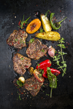 Barbecue T-bone lamb steak with Vegetable and seasonings on a rusty metal sheet Stock Photo - 86470009